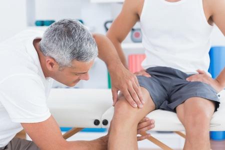 doctor examining knee